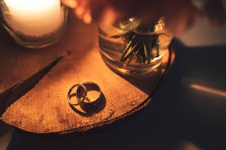 Top view of wedding rings couple laying on wooden slice of tree trunk in candle light. Warm orange toned colors.