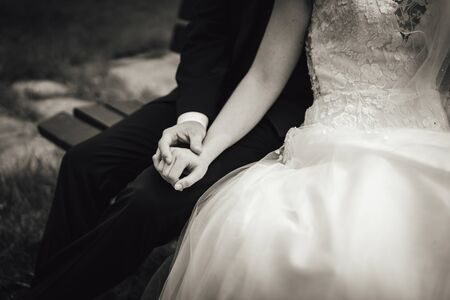 Black and white photo of marriage couple sitting on bench. Close up of holding hands on grooms knee. Without head. Wedding day concept.