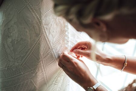 Bridesmaid helping bride to dress wedding gown. Close up of hands fastening buttons on lace wedding dress. Wedding day concept.