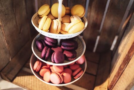 Three tiered plate stand with colorful sweet macaroons. Wooden plant box background. Dessert for served with afternoon tea or coffee. Wedding or party