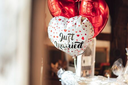 Romantic group of inflated plastic balloon in heart shape. One white piece with red hearts and lettering