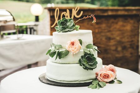 Close up of white wedding cake laying on table. Love inscription, pink rose and green leaves floral decoration. Outside terrace. Wedding day concept.