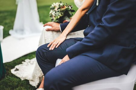 Marriage couple sitting on chairs at wedding ceremony. Bride and groom touching each others knees close up. Stock fotó