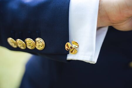 Close up of mans hand with golden propeller cufflinks on shirt and gold color buttons with anchor sign on blue suit. Fashion, formal clothing concept Stockfoto