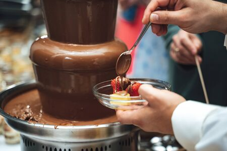Chocolate fondue fountain. Man gathering sweet chocolate. Close up male hand holding fresh fruit in glass dish and pouring chocolate with spoon on it.