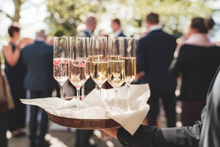 Formal clothed man hand holding tray with several glasses of white wine. Champagne with berries. Blurred guests in background. Celebration, party