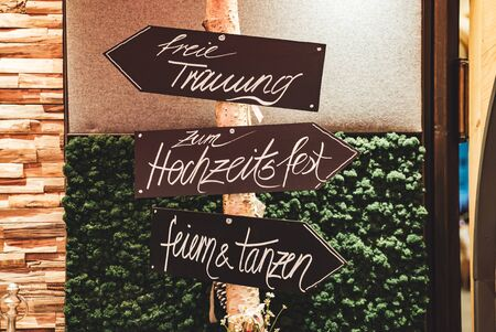 Signpost with german inscriptions for guests at wedding.Signs directing with arrows where to go for wedding ceremony, wedding feast, celebrate & dance