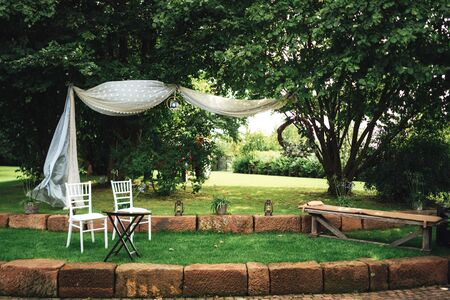 Wedding decoration prepared for ceremony in garden or park.Two white chairs on lawn in park. Outdoor nuptials. Wedding day concept.