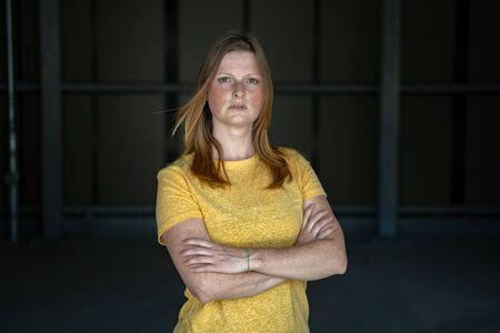 Portrait of european freckled woman standing with folded hands over dark background. Worrying expression in female face. Stock Photo