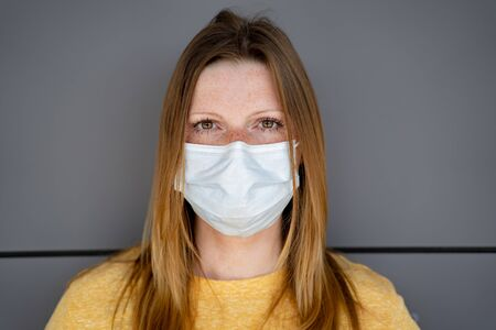 Caucasian woman wearing white disposable surgical face mask. Grey wall in background. Corona virus pandemic protection concept.