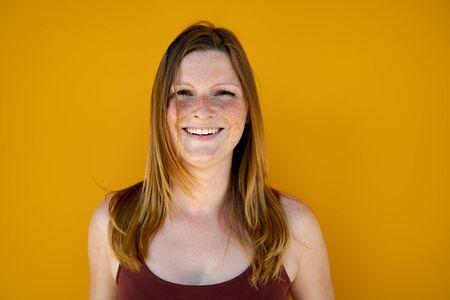 Beautiful joyful woman portrait. Smiling long-haired female wearing burgundy top over yellow background. Selective focus.