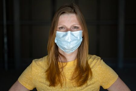 Woman wearing surgical disposable face mask to prevent spreading disease looking to camera. Corona virus pandemic protection concept. 版權商用圖片
