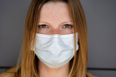 Closeup of female face with white disposable surgical face mask. Grey wall in background, selective focus. Corona virus pandemic protection concept.