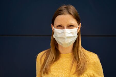 Woman wish surgical disposable face mask to prevent spreading disease standing in front of blue wall. Corona virus pandemic protection concept. 版權商用圖片