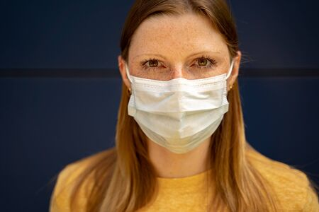 Closeup of european woman with serious expression on her face wearing white protective face mask. Corona virus pandemic protection concept. 版權商用圖片 - 150423904