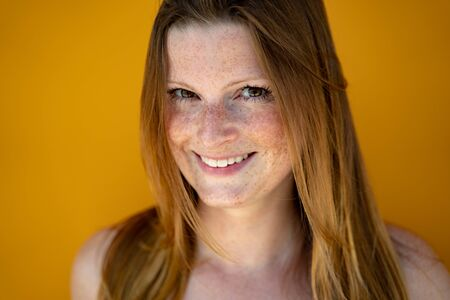 Face closeup of smiling european woman looking to camera. Likeable long-haired lady over yellow background. Banque d'images