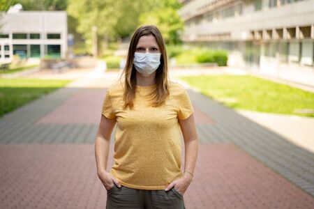 Woman in leisure time clothes wearing disposable protective face mask standing on colorful pavement. Corona virus pandemic protection concept.