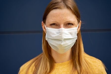 Masked woman smiling under surgical disposable face mask. Blue background. Corona virus pandemic protection concept. 版權商用圖片