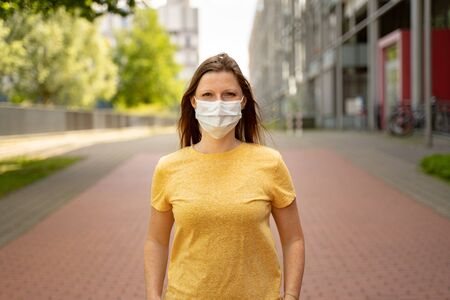 Woman wearing surgical disposable face mask to prevent spreading disease standing in town street. Corona virus pandemic protection concept.