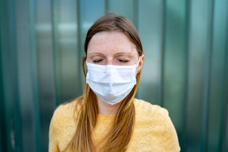 Exhausted caucasian woman with closed eyes wearing white disposable face mask to avoid Covid-19 disease. Corona virus pandemic protection concept. 版權商用圖片