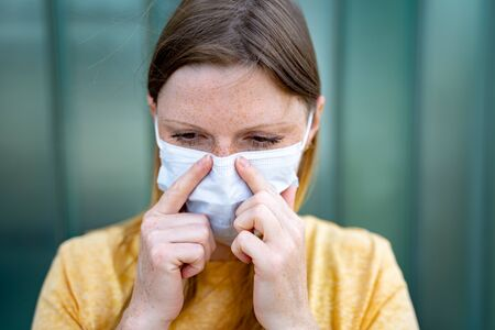 Closeup of female face. Tired woman adjusting her disposable protective face mask at nose. Corona virus pandemic protection concept.
