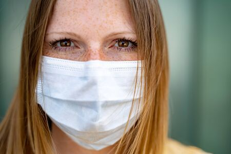 Closeup of woman face. Female wearing white single-use protective face mask. Selective focus. Corona virus pandemic protection concept.