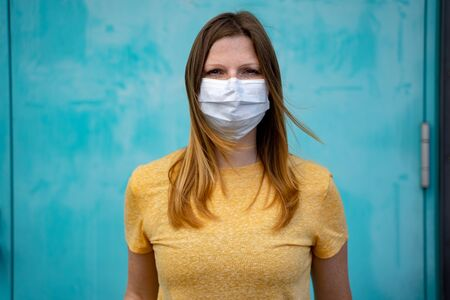 Portrait of beautiful woman wearing white surgery mask to avoid Covid-19 disease. Light blue background. Corona virus pandemic protection concept.