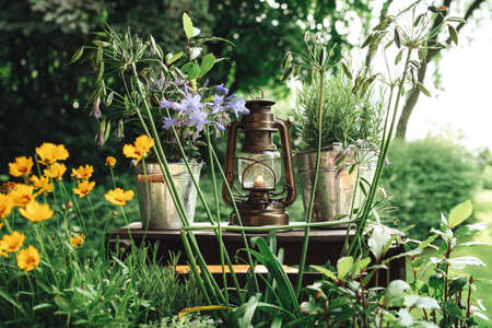 Vintage oil lantern standing on wooden base in park surrounded by flowers and green vegetation. Outdoor photo.