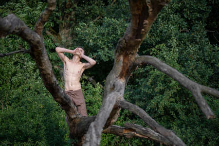 Shirtless man with head in hands kneeling on log against trees at forest