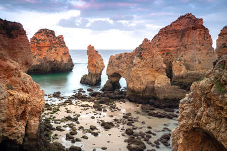 Scenic view of rock formations at beach against sky Imagens