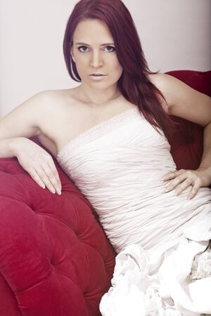 young red haired beautiful bride on red sofa  photo