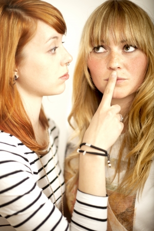 mouth couple: red haired and blond girl sign to shut up with finger