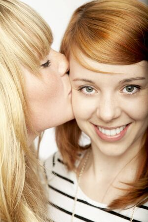 blond girl give red haired girl kiss and smile Stock Photo - 14530091