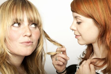 two beautiful girls looking at blond and red hair Stock Photo - 14530088