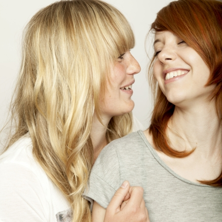 cute little girls: blond and red haired girls are laughing and have fun Stock Photo
