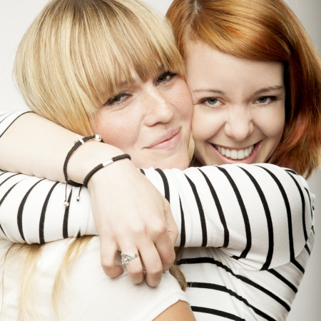 friends happy: red and blond haired girls friends laughing and hug Stock Photo