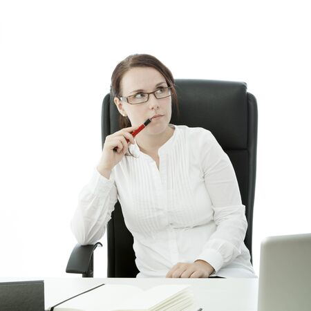 young brunette businesswoman with glasses and pen thinking on desk photo