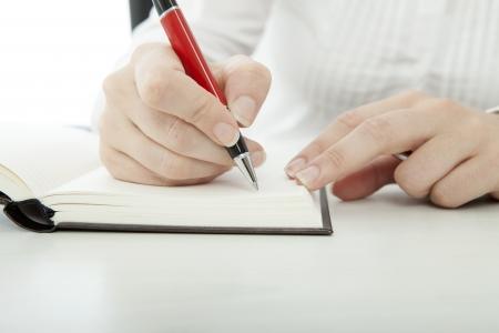 jonge brunette zakenvrouw met een bril het invoeren van tekst in het boek met pen Stockfoto