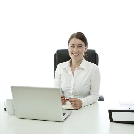 jonge brunette zakelijke vrouw lachend achter het bureau Stockfoto