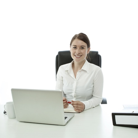 young brunette business woman smiling behind desk