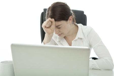 jonge brunette zakelijke vrouw is gefrustreerd achter laptop
