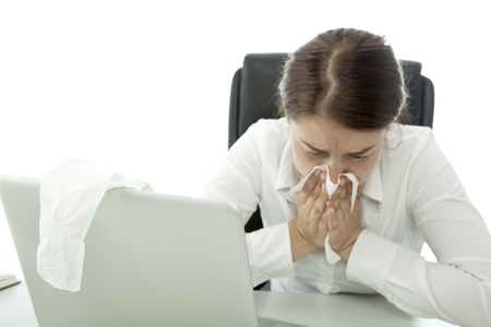 young brunette business woman is ill with hankies behind laptop Stock Photo - 14656576
