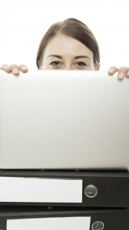 young woman hiding behind laptop and documents photo