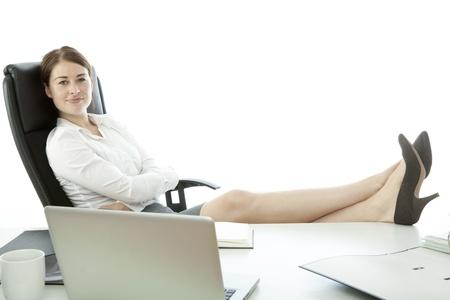 pied jeune fille: jeune femme d'affaires avec des pieds sur le bureau souriant