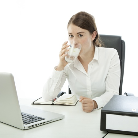 young brunette business woman is drinking water in front of desk photo