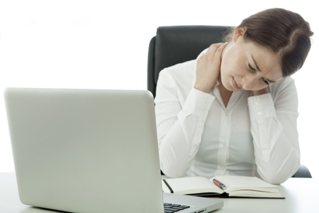 neck pain: young brunette business woman pain neck behind computer
