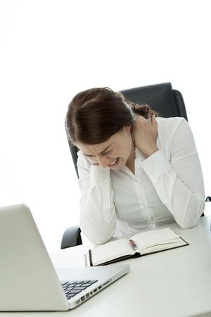 jonge brunette zakenvrouw nekpijn op het bureau Stockfoto