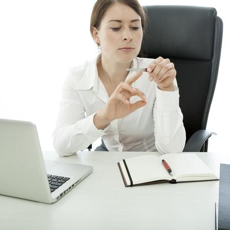 jonge brunette zakenvrouw bestand nagels tijdens het werk Stockfoto