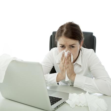 estornudo: mujer de negocios joven morena est� enfermo con pa�uelos detr�s de la computadora port�til