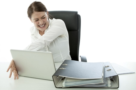 young brunette business woman in rage and throw laptop desk photo
